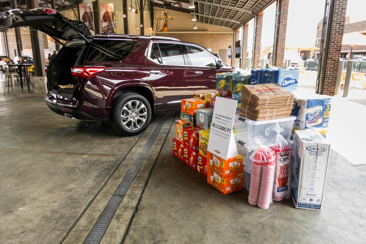 exterior view of a red 2018 chevrolet traverse next to a large pile of cargo being used to demonstrate cargo space