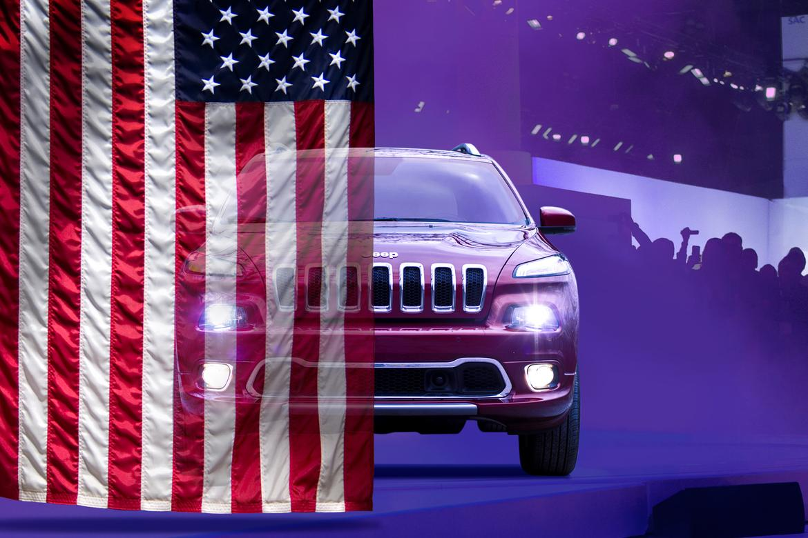 Front view of a red Jeep Grand Cherokee with an American flag covering the left half of the image