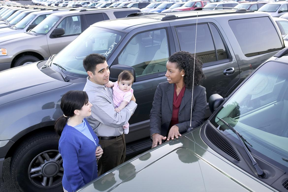 Two parents, with Dad holding baby talking to a car saleswoman