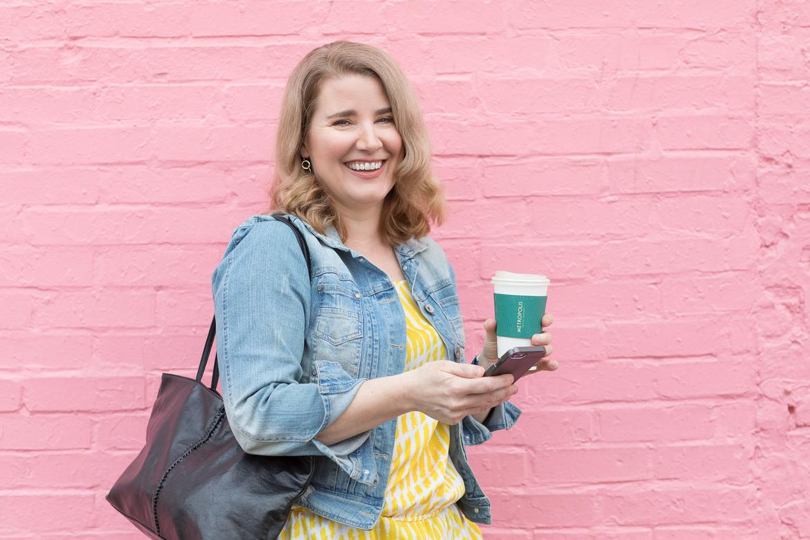 Smiling woman holding coffee and phone, in front of pink wall