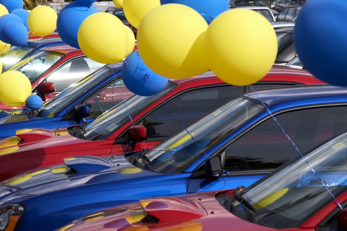Cars in a dealer lot with balloons.