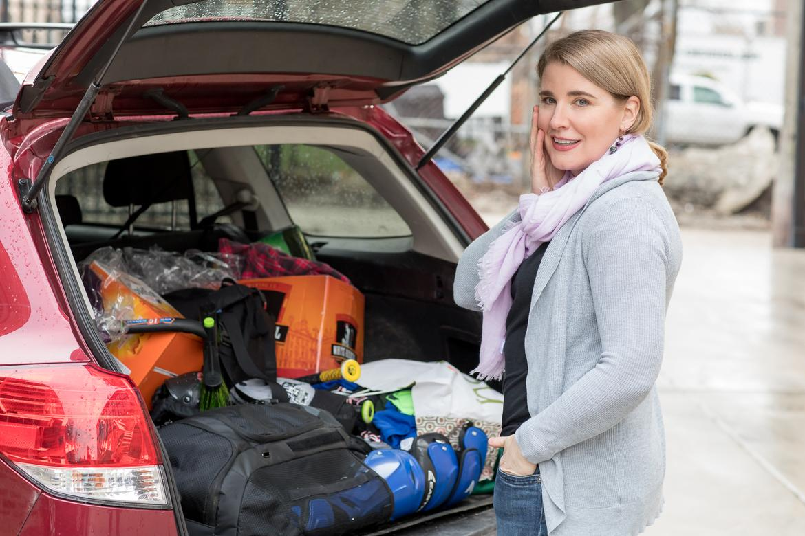 Woman with concerned look standing in front of cluttered car trunk