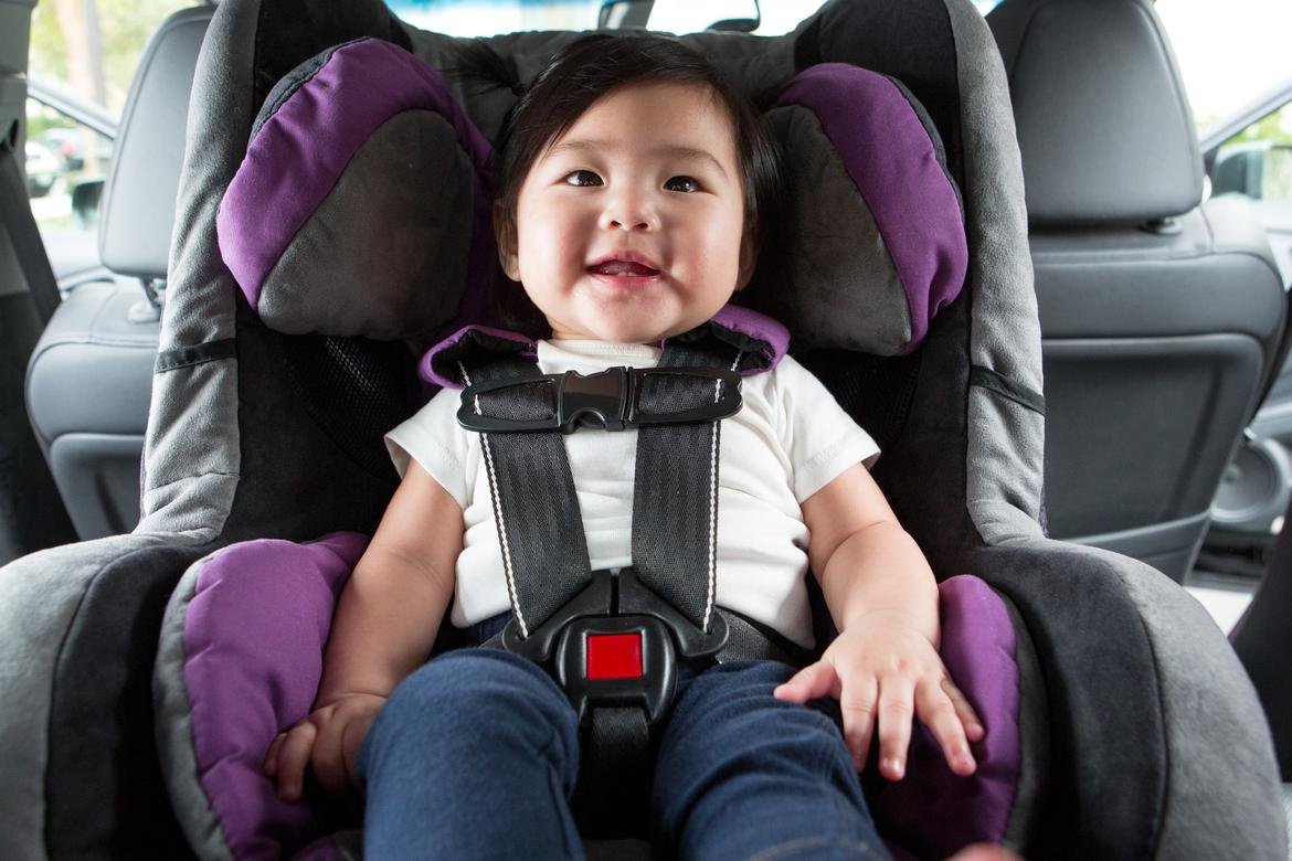 Smiling baby sitting in carseat